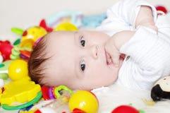 Mooie vier-maanden baby onder speelgoed Royalty-vrije Stock Fotografie