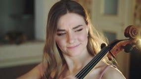 Mooie violoncellist zitting op bed en het spelen van de melodie in slaapkamer stock videobeelden