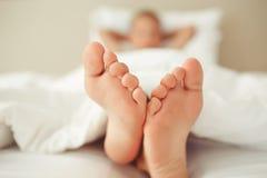 Mooie voeten van een klein kind die onder een witte deken, close-up liggen Stock Afbeelding