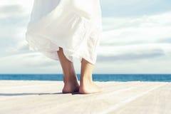 Mooie voeten van een vrouw in witte kleding op een houten pijler Overzeese en Hemelachtergrond royalty-vrije stock fotografie
