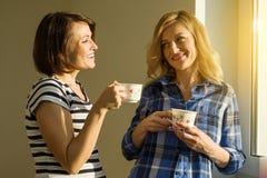 Mooie volwassen vrouw die hete koppen die van koffie het drinken houden, zich dichtbij het venster bevinden Stock Fotografie