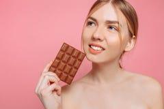 Mooie vrolijke jonge vrouw die een bar van zwarte chocolade op een roze achtergrond houden royalty-vrije stock afbeelding