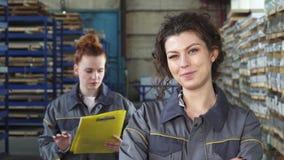 Mooie vrolijke vrouwelijke fabrieksarbeider die aan de camera glimlachen stock videobeelden