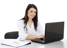 Mooie vrouw arts die aan laptop en het glimlachen werkt Stock Afbeelding