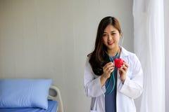 Mooie vrouw arts met het hart van de stethoscoopholding stock afbeelding