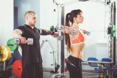 Mooie vrouw bij de gymnastiek die met haar trainer uitoefenen Mooie vrouw Stock Foto