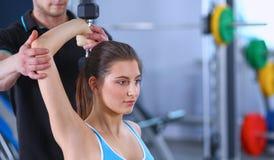 Mooie vrouw bij de gymnastiek die met haar trainer uitoefenen Stock Afbeelding