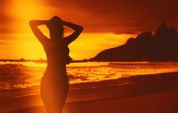 Mooie vrouw in bikini bij strand na het zwemmen bij zonsondergang Royalty-vrije Stock Foto's