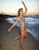 Mooie vrouw in bikini bij zonsondergang op het strand Stock Foto