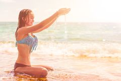 Mooie vrouw in bikini die bij de kust zonnebaden royalty-vrije stock foto's