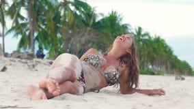 Mooie vrouw in bikini die op zandig strand en gietend zand op uw lichaam liggen Sexy vrouw die zand op gelooid haar uitstrooien stock footage