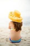 Mooie vrouw in bikini en het gele hoed ontspannen bij strand Stock Foto