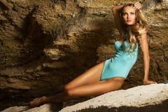 Mooie vrouw in blauwe bikini op de rots Royalty-vrije Stock Fotografie