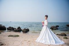 Mooie vrouw in de holdingsbloem van de huwelijkskleding stock fotografie