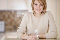 Mooie vrouw in de keuken met een glas water Stock Foto