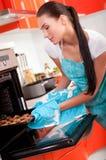 Mooie vrouw in de koekjes van het keukenbaksel. Stock Fotografie