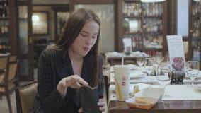 Mooie vrouw in de kostuumzitting in het restaurant die snel voedsel eten Aantrekkelijke donkerbruine dame het drinken kola en het stock video