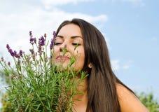 Mooie vrouw in de tuin ruikende bloemen. stock afbeelding