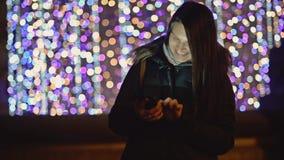 Mooie Vrouw in de Winter Donkere Laag met Smartphone in de Nachtstad op de Achtergrond van Kerstmislichten Het glimlachen brunett stock video