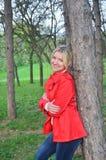 Mooie vrouw dichtbij de boom in het rode jasje Stock Fotografie