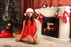 Mooie vrouw dichtbij de open haard in de winterhuis selebrating Kerstmis Stock Fotografie