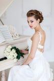 Mooie vrouw dichtbij de witte piano stock fotografie