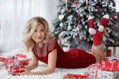 Mooie vrouw dichtbij een Kerstboom met een kop van koffie met heemst Royalty-vrije Stock Fotografie