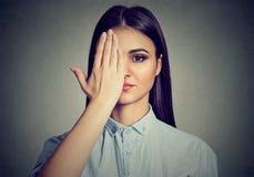 Mooie vrouw die één oog behandelen met hand stock afbeelding
