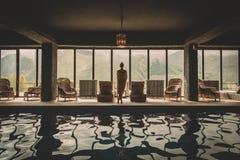 Mooie vrouw die aan de mening van bergen in de ruimten met zwembad en panoramische vensters kijken stock foto