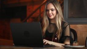 Mooie vrouw die aan haar laptop op een modieus stedelijk restaurant werken stock videobeelden