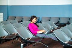Mooie vrouw die aan laptop bij de luchthaven werken royalty-vrije stock afbeelding