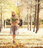 Mooie vrouw die alleen in het de herfstpark met een boek zijn Stock Afbeeldingen