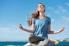 Mooie vrouw die bij de kust mediteert Stock Fotografie