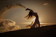 Mooie vrouw die bij gouden zonsondergang dansen stock afbeelding