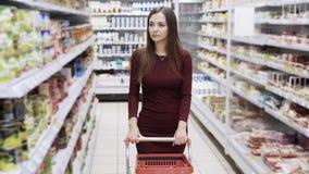 Mooie vrouw die bij supermarkt winkelen, steadicam schot stock footage