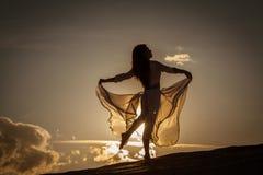 Mooie vrouw die bij zonsondergang dansen royalty-vrije stock afbeelding