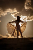 Mooie vrouw die bij zonsondergang dansen stock foto