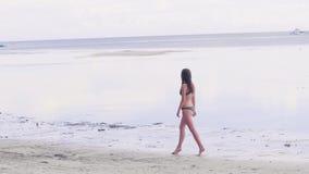 Mooie vrouw die in bikini op zandige kust op overzees strand lopen Jonge vrouw die de zomer van gang op nat zand genieten bij str stock video