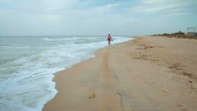 Mooie vrouw die blootvoets door het overzeese strand in winderig weer lopen stock videobeelden
