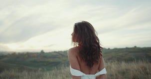 Mooie vrouw die in bruidkleding in het midden van landschap lopen stock footage