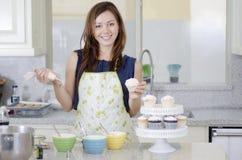 Mooie vrouw die cupcakes maken Royalty-vrije Stock Afbeeldingen