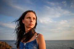 Mooie vrouw die de afstand onderzoeken bij zonsondergang tegen de hemel stock fotografie