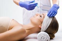 Mooie vrouw die in de kliniek, een plastic chirurg in de handen van de naald liggen Stock Foto