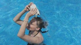 Mooie vrouw die in de pool met overzeese shell glimlachen stock footage