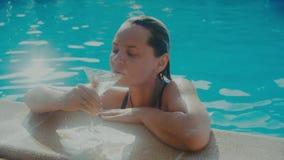 Mooie vrouw die dichtbij de pool van haar vakantie met genieten glazen van martini stock footage