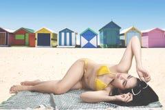 Mooie vrouw die dichtbij het plattelandshuisje zonnebaden Royalty-vrije Stock Foto