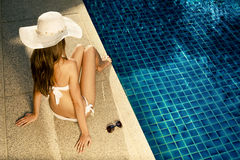 Mooie vrouw die dichtbij zwembad zonnebaden Royalty-vrije Stock Afbeelding