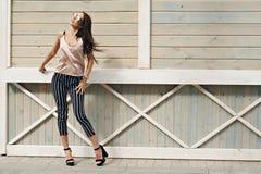 Mooie vrouw, die donkere glazen dragen, tegen de achtergrond van een boommuur Het model draagt modieuze beige kleren, Royalty-vrije Stock Foto