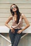 Mooie vrouw, die donkere glazen dragen, tegen de achtergrond van een boommuur Het model draagt modieuze beige kleren, Stock Foto