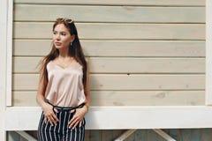 Mooie vrouw, die donkere glazen dragen, tegen de achtergrond van een boommuur Het model draagt modieuze beige kleren, Royalty-vrije Stock Afbeeldingen